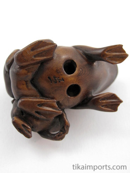 handcarved boxwood netsuke of three frogs showing hole through underside