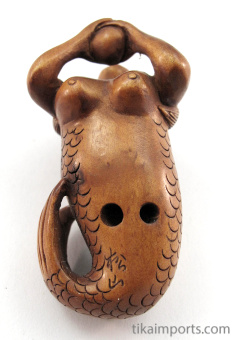 handcarved boxwood netsuke of mermaid holding a pearl showing hole through underside of tail
