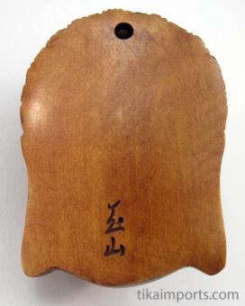 handcarved boxwood netsuke of buddha face showing hole through reverse side