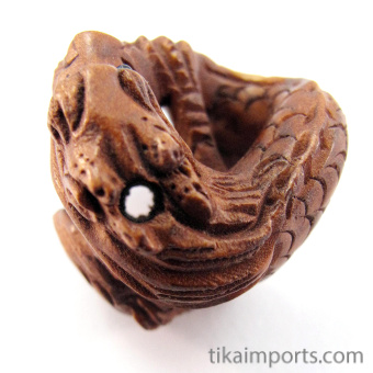 handcarved boxwood ojime bead of dragon showing hole from top to bottom