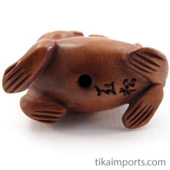 handcarved boxwood ojime bead of seal showing hole through center of body