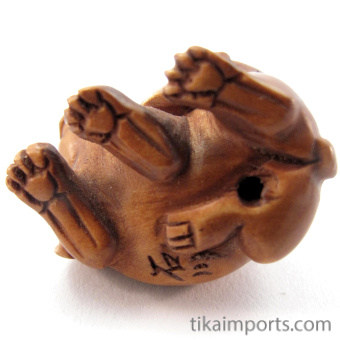 handcarved boxwood ojime bead of bunnies showing hole through center of body