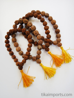 Natural rudraksha seed beads, strung into a stretch bracelet with elastic cord and tassel- showing variety