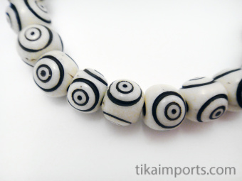 Handcarved waterbuffalo bone beads strung into a stretch bracelet with elastic cord and tassel