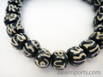 Mala stretch bracelet with batik bone beads featuring the sanskrit symbol 'Om'