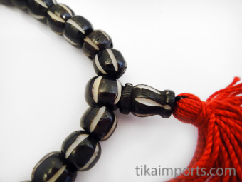 Dark handcarved waterbuffalo bone beads strung into a stretch bracelet with elastic cord and tassel