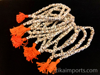 Small fine handcarved bone skull beads strung into a stretch bracelet with elastic cord and tassel, showing group of 10pcs
