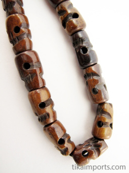 Dark handcarved bone skull beads strung into a stretch bracelet with elastic cord and tassel