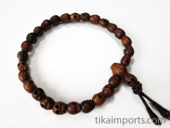 Tiny handcarved wood skull beads strung into a stretch bracelet with elastic cord