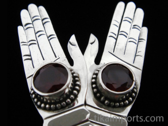 Sterling silver hand-shaped earrings featuring faceted garnet stones