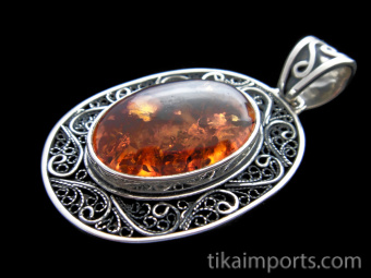 Sterling silver pendant featuring amber framed in elaborate filigree setting