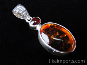 Sterling silver pendant with woven pattern on bail featuring amber and garnet accent stone