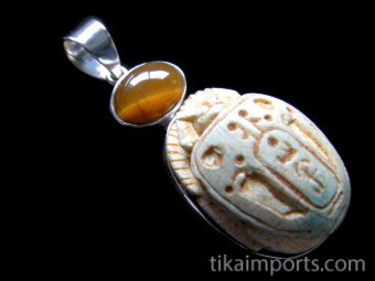 Tigers eye cabochon set above intricately carved faience scarab