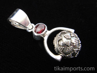 Sterling silver pendant featuring a handmade granulated silver bead suspended below garnet accent stone