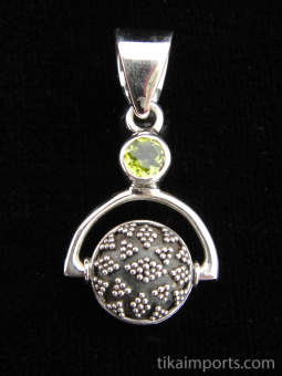 Sterling silver pendant featuring a handmade granulated silver bead suspended below peridot accent stone