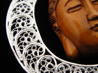 Sterling silver pendant featuring a handcarved Quan Yin ojime bead suspended in a filigree crescent-shaped setting