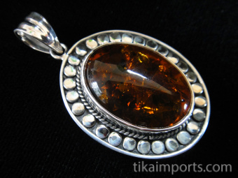 Sterling silver pendant featuring amber framed in a decorative setting