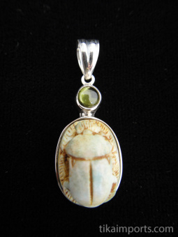 Sterling silver pendant featuring a carved faience scarab with peridot accent stone