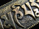 closeup of Om Mani Padme Hum brass pendant, a universal prayer for peace
