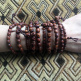 Wood Skull Mala Bracelets being worn - showing variety in a typical 10pc assortment