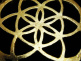 closeup of gold-toned brass pendant with Seed of Life design from Sacred Geometry Tradition