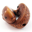 handcarved boxwood ojime bead of double fish showing hole through both fish