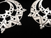 Closeup of handcrafted brass earrings plated in sterling silver with solid sterling silver earwires