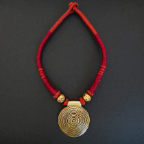 handmade cotton necklace featuring brass disc pendant inspired by traditional pieces from Nagaland