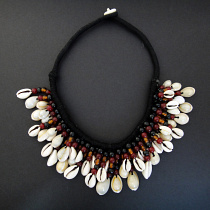 Cowrie Dancer Necklace with colorful glass and natural cowrie shell beaded fringe on a cotton cord