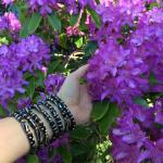 batik bone bracelets being worn in front of purple rhododendron