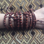 a 10pc assortment of wood skull bracelets, shown being worn