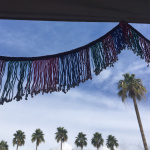 textiles on display with Tucson palm trees in the background