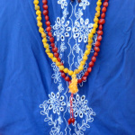Knotted Haldi Turmeric and Red Heart Seed Mala shown being worn