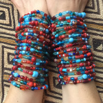 Arctic Sunrise stretch bracelets being modeled over a Kuba Cloth
