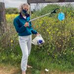 Tika girl picking up trash while wearing a Tika silk face mask