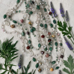 flat lay with herbs and tumbled crystal multistrand necklace