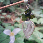silver pendant on display in nature