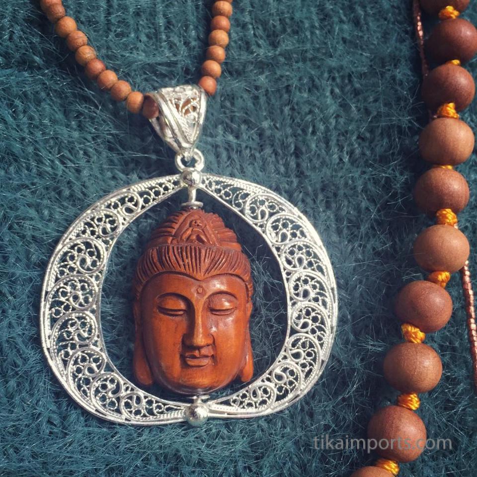 filigree silver pendant featuring handcarved boxwood ojime bead worn with sandalwood mala