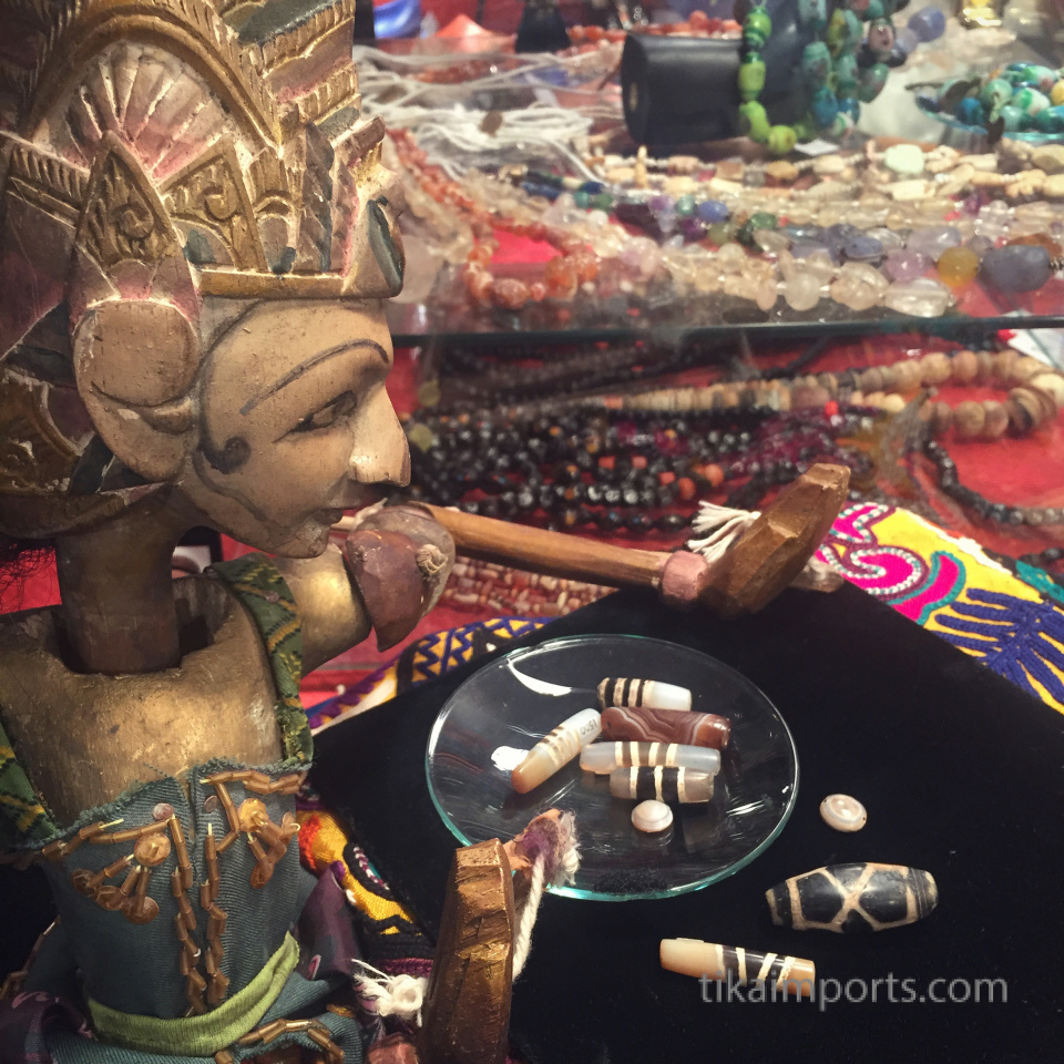 vintage wayang puppet looking through a dish of ancient beads