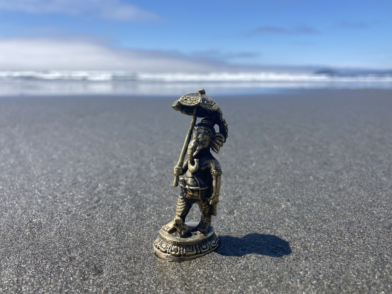 brass statue of Ganesh with umbrella on the beach