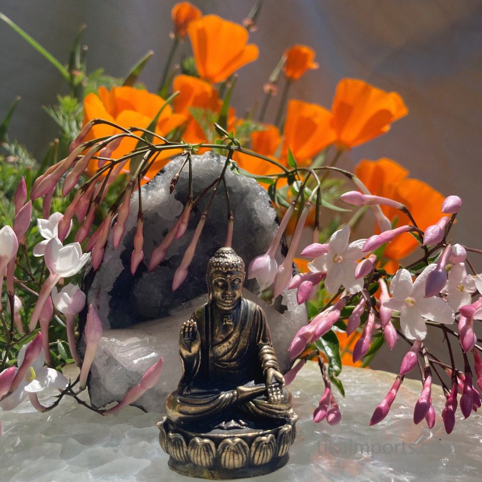 large brass statue of Buddha sitting in meditation, surrounded by an altar of natural flowers and crystals